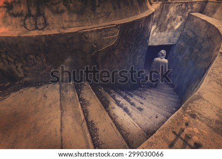 Strange figure descends the stairs underground  - stock photo