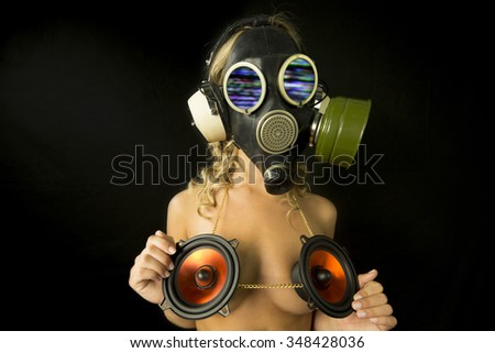 strange gas mask disco gogo dancer with audio speakers covering breasts, focus not on mask - stock photo