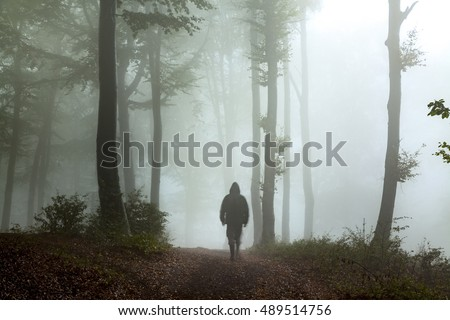 Strange man in misty scary forest