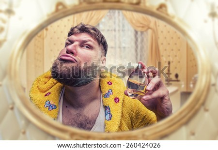 Strange man perfumes himself looking in the mirror - stock photo