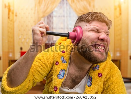 Strange man with a plunger in his ear - stock photo