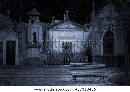 Strange old european dark cemetery with a bench in the foreground