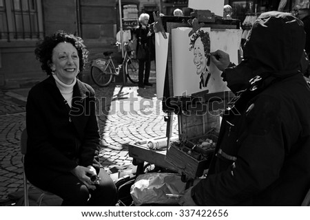 Strasbourg, France - 05 April 2015: Cartoonist draws a caricature of a woman on the streets of Strasbourg, France on 05 April 2015.