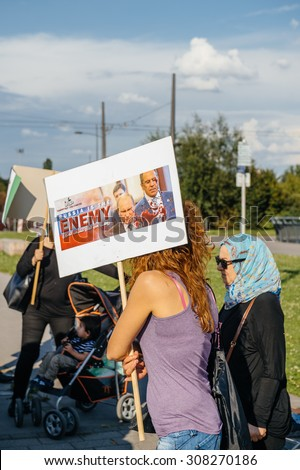 STRASBOURG, FRANCE - AUG 20, 2015: People protesting in front of European Parliament denouncing the Syrian airstrikes on Douma wheremore 80 were killed - Russia is the enemy placard - stock photo