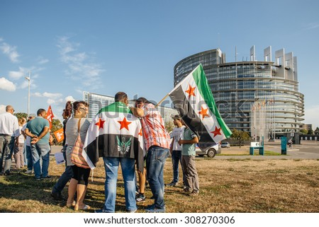 STRASBOURG, FRANCE - AUG 20, 2015 People protesting in front of Parliament denouncing the Syrian airstrikes on Douma wheremore 80 were killed - flag of Syria with Parliament building in the background - stock photo