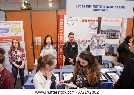STRASBOURG, FRANCE - FEB 4, 2016: Children and teens of all ages attending annual Education Fair to choose career path and receive vocational counseling - youth group choosing at stand - stock photo