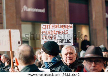 STRASBOURG, FRANCE - 11 JAN, 2015:  People hold placards reading 'Catholics, muslims, jews all are Charlie' during a unity rally (Marche Republicaine) where some 50000 people took part - stock photo