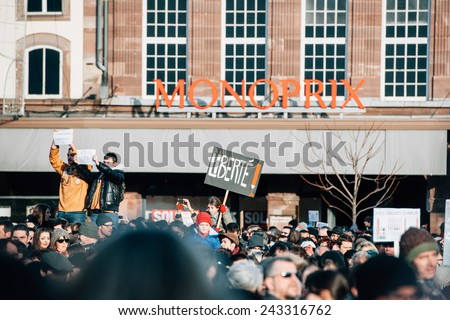 STRASBOURG, FRANCE - 11 JAN, 2015:  People hold placards reading 'Freedom' during a unity rally (Marche Republicaine) where some 50000 people took part in tribute three-day killing spree in Paris