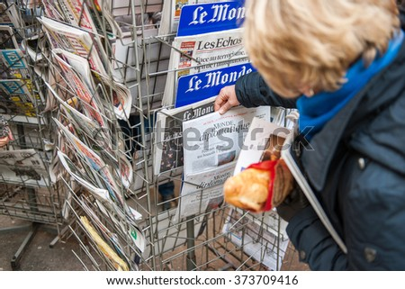 STRASBOURG, FRANCE - JAN 10, 2015: Woman holding french baguette selecting Le Monde Diplomatique magazine on the kiosk press stand - stock photo