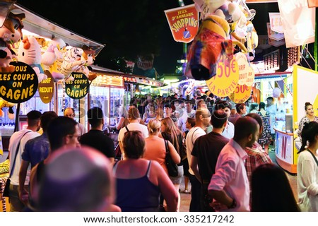 STRASBOURG, FRANCE - JULY 19, 2015: Crowd of people late night in amusement park admiring diverse offers - stock photo