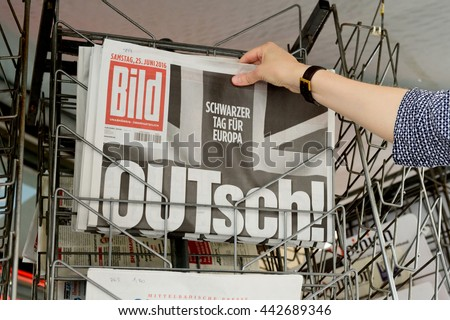 STRASBOURG, FRANCE - JUN 25, 2016: Woman buying Bild Magazine newspaper with shocking headline titles at press kiosk about the Brexit requesting to quit the European Union - stock photo