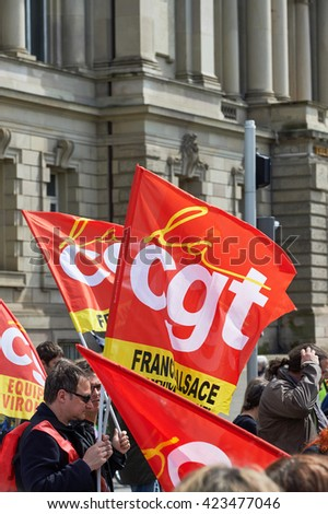 STRASBOURG, FRANCE - MAY 19, 2016: Crowd with placards and CGT flags on closed street during a demonstrations against proposed French government's labor and employment law reform - stock photo