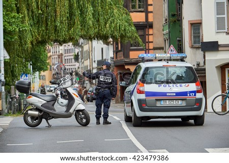 STRASBOURG, FRANCE - MAY 19, 2016: Frenc police officer securing roate during a demonstrations against proposed French government's labor and employment law reform - stock photo