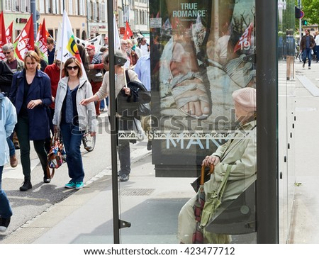STRASBOURG, FRANCE - MAY 19, 2016:Senior woman watching protestors marching on closed street during a demonstrations against proposed French government's labor and employment law reform - stock photo