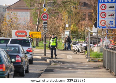 STRASBOURG, FRANCE - NOV 14 2015: French Police checking vehicles on the 'Bridge of Europe' between Strasbourg and Kehl Germany, after attacks in Paris - two officers inspecting cars