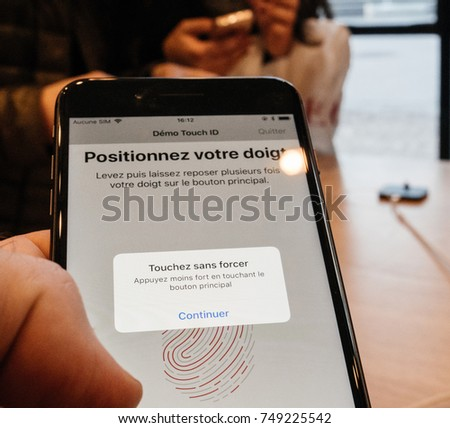 STRASBOURG, FRANCE - NOV 3, 2017: Man trying the Touch ID function on the latest iPhone 8