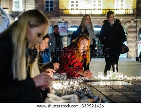 STRASBOURG, FRANCE - 14 NOV 2015: Woman light candles in the center of Strasbourg for the victims of the November 13 attacks in Paris that killed at least 128 people - stock photo