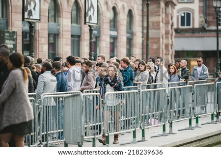 STRASBOURG, FRANCE - SEPTEMBER 19, 2014: A woman leaving the long waiting line outside the Apple Inc. store during the sales launch of the iPhone 6 and iPhone 6 Plus in Europe, on Sept. 19, 2014 - stock photo
