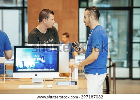 STRASBOURG, FRANCE - SEPTEMBER 19, 2014: An Apple Inc. genius employee assists a customer with the purchase during the sales launch of the iPhone 6 and iPhone 6 Plus at the company's store in France. - stock photo