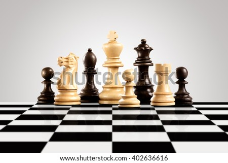 Strategy and leadership concept; black and white wooden chess figures standing on the board ready for game. - stock photo