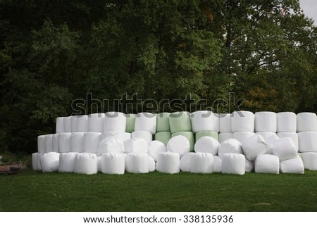 straw bale wrapped in plastic piled up by trees