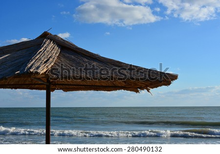 Straw Beach Umbrella, sea and blue sky with clouds