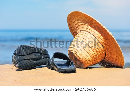 Straw hat and rubber flip-flops on the seashore  - stock photo