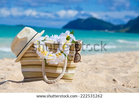 Straw hat, bag, sun glasses and flower lei garland of white plumeria on a tropical Hawaiian beach. - stock photo
