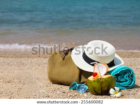 Straw hat, sunglasses, beach towel with beach bag and coconut cocktail. Summer travel and vacation concept - stock photo