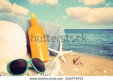 Straw hat,sunglasses, towel and starfish on sand beach. - stock photo