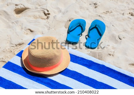 Straw hat, towel and flip flops on a tropical sand beach - stock photo