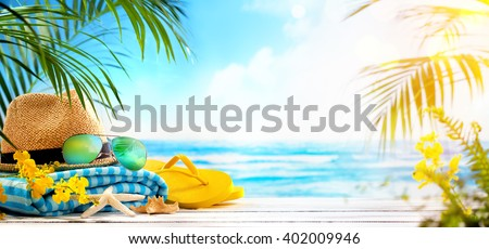 Straw hat, towel, sun glasses and flip flops on beach - stock photo