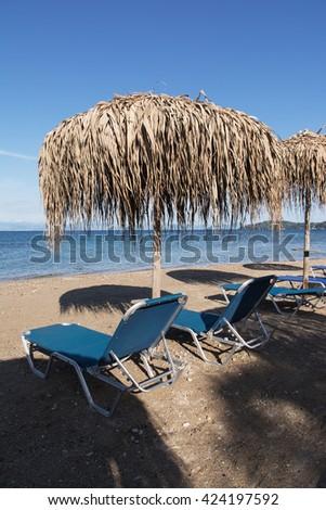 Straw umbrellas and sunbeds on a sandy beach, Corfu, Greece - stock photo