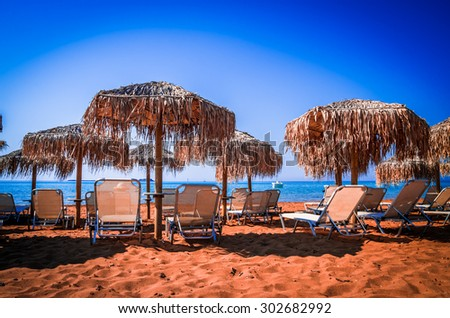 Straw umbrellas and sunbeds on a sandy beach in Greece. Parasols and tanning beds on the beach.  - stock photo