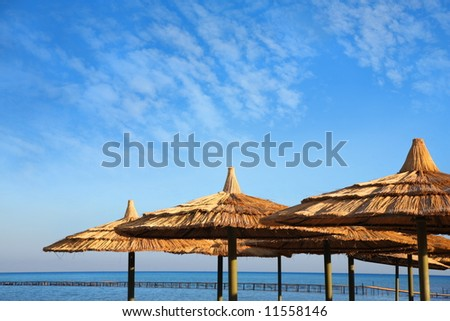 straw umbrellas on blue sky and sea with pier
