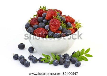 Strawberries and blueberries in a white bowl