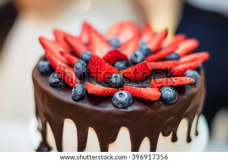 strawberries and blueberries on chocolate cake closeup - stock photo