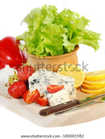 Strawberries and cheese on a wooden plate