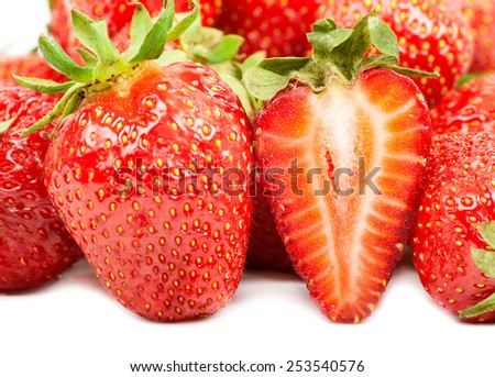 strawberries and half of the berries on the large background of ripe berries - stock photo