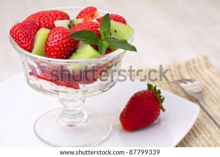 strawberries and kiwi on a white table.
