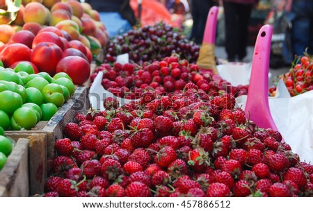 strawberries and plums at fruits market
