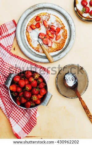 Strawberries and whipped cream  for dessert. Pancakes with  strawberries and sour cream. Stack of pancakes with fresh strawberry and balsamic glase in frying pan on wooden table. Rustic style - stock photo