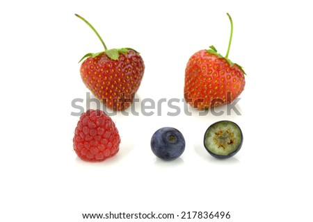 Strawberries, blueberries and a raspberry isolated on white - stock photo