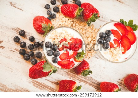 Strawberries, blueberries and breakfast cereal in yogurt on a wooden rustic table - stock photo