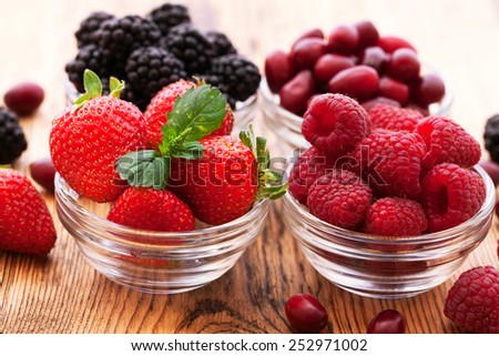 strawberries, blueberries, blackberries and raspberries in bowls, top view, close-up Selective focus - stock photo