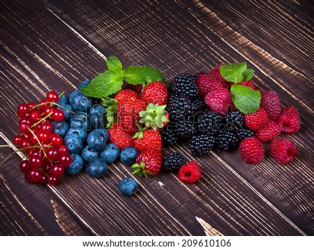 Strawberries, blueberries, blackberries, raspberries and currant on wooden background - stock photo