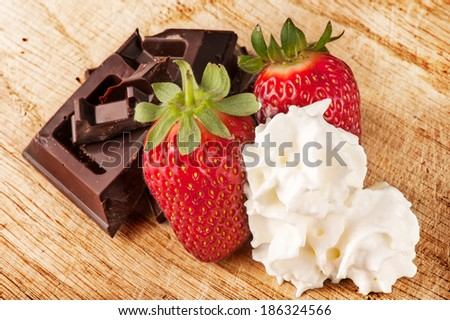 Strawberries, chocolate bar in pieces and cream - stock photo