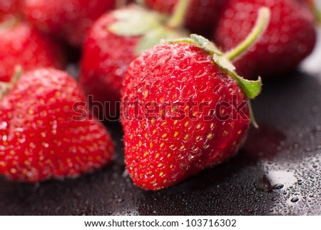 Strawberries Composition on black, macro shot - stock photo