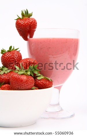Strawberries in a bowl and a strawberry shake in a glass decorated with a strawberry on white background