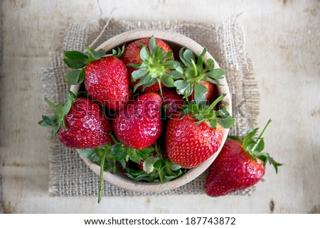Strawberries in a Bowl, on a wooden background - stock photo